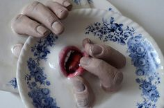 "Israeli ceramicist Ronit Baranga's ""body of work"" is unsettling, to say the least. Sculpted from clay, realistic fingers emerge from plates while mouths lurk inside cups. The gnarled fingers and lips seem poised for action. We would most certainly hesitate before using any of these for fear of being"