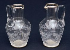 BACCARAT - Par de lindas jarras de coleção em cristal francês ricamente lapidado com borda e base prata contrastada. Med.: 17 cm. Base 580,00