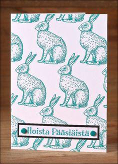 Valkoiselle korttipohjalle on leimattu pupuja turkoosilla musteella. Iloista Pääsiäistä on leimattu erilliselle valkoiselle kartonkipalaselle myöskin turkoosilla musteella.
