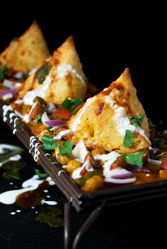 Samosa Chaat - A delicious dish of chole and samosas, topped with chopped tomatoes, onions, cilantro, yogurt, savory and sweet chutney, and fine sev.