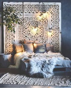 Boho bedroom furs Gawd, do I ever love this lush, bohemian chic bedroom! The wonderful and large-scale architectural piece that acts as a headboard makes me think of Moorish castles, or perhaps Marrakesh. Such a wonderful mishmash, with furs over a shabby-chic palette bed! Lots of texture and pattern in this monochromatic space. And lighting is wonderfully absurd and informal yet sensual...