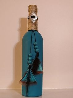 Southwest style wine bottle, painted turquoise, wrapped with twine, and embellished with feathers, turquoise beads, and a silver concho. Add a bit of the southwest to your home decor with this hand-painted wine bottle.