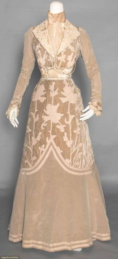"VELVET & WOOL AFTERNOON GOWN, c. 1902. 2-piece, taupe moire silk faille & velvet w/ faun wool flannel appliques in stylized folige motifs, bolero style bodice, high neck ""under bodice"" of cream silk panne, ribbon embroidered & lace trimmed lapels, lace jabot.  Front"