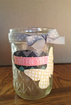 Mason jar decorated with scrapbook paper and attached with mod podge.