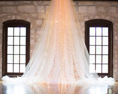 This elegant wedding backdrop is made from oodles of tulle and lights! This is 1 full panel which is hand sewn and assembled with the lights, making it even easier for you to decorate for your special day! Perfect for Wedding ceremonies, bridal showers or baby showers! See all our other listings in our shop! https://www.etsy.com/shop/CraftyCousinsCo  This back drop pictured is 11 feet tall by 3 to 5 feet wide depending on how far you stretch it out. The fabric itself is 22 feet wide per…