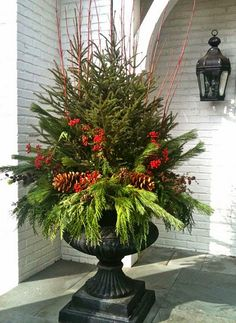black urn with christmas greens and red berries christmas crafts christmas planters christmas arrangements