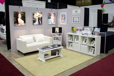 """I like the simplicity of it! Would change the wall color, but I love the cube shelf, """"tv"""" display stand idea, the couch and coffee table. But I doubt this is an 8x10 booth. Looks larger."""