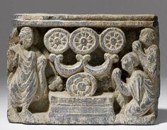 LE PREMIER SERMON DU BUDDHA  Art du Gandhâra ca 2°- 4° siècle  Schiste.  11 x 15 cm  Rare relief présentant le Buddha debout et deux attendants agenouillés devant un trône sur lequel repose une roue stylisée en forme de lotus épanoui en supportant trois autres.  Cette symbolique évoquant la période aniconique de l'iconographie bouddhiste est bien évidemment à mettre en rapport avec le premier sermon du Buddha dans le parc des gazelles de Sarnath qui était composé de trois parties.