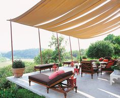 Canopy style shades cover a lovely outdoor terrace that overlooks a hillside! Love the Moroccan...