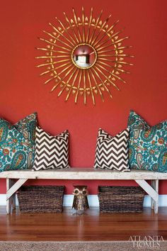 Bench w/ fun pillows under Elephant photo w/ baskets for dog toys in between living and dining room