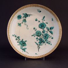 "An 18th Century White Chinese Export Porcelain Saucer-Dish. The London Decoration was Probably Added at the Workshop of James Giles (1718-1780) c.1760-165. The Painting in Green with Black Out-lines is of Loosely Arranged Garden Flowers. The Bright Gilding is of a Design Attractively Categorized by Stephen Hanscombe as ""An Elaborate Gilt Tasseled Bird`s Eye Border""."