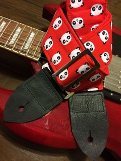Cool guitar strap -- cute cartoon pandas -- black and white on a red background by MyMumDrivesaUFO on Etsy