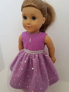 This cute little dress is inspired by the 2018 American Girl Doll of the year, Luciana. It features sparkly stars and moons on purple tulle and purple background. A pretty silver ribbon is sewn around the waist. I have also made an optional silver star necklace. The dress is easy to