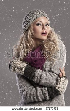 attractive young woman in a winter fashion shot wearing a wool cap, a grey woolen sweater and a purple scarf - stock photo
