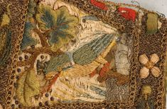 embroidered gauntlet panel circa 1600, inset with satin panels embroidered with kingfishers and cranes within lavish couched silver and gold thread borders with raised floss silk florets and pea pods of couched silver and shaded green silk threads which open, the eight green tabs embroidered with moss green foliage and edged in spangled fringes,