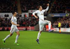 Gylfi Sigurdsson leaps in the air to celebrate opening the scoring for Swansea with his fi...