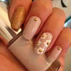 Nude base and gold glitter on index finger, daisies on ring finger with a gold gem in the center.