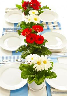 """""""For year-round color, paint your picnic table white with a couple of blue planks. Add festive July 4 touches with potted flowers such as the gerbera daisies shown here and an assortment of blue napkins. Blue Table Settings, A Table, Picnic Table, Picnic Potluck, Summer Picnic, Celebrate Good Times, Red Flowers, Potted Flowers, Event Decor"""