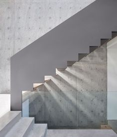 Concrete staircase outside a house featuring protruding glass boxes that offer ocean views to its residents.