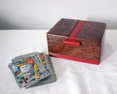Great vintage wooden box with an Art Deco style serves as a snug storage container for six decks of playing cards. The box has a burled wood look and carved grooves, painted red, around the bottom and in a stripe across the top, plus a long round red bakelite knob for opening the lid.