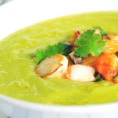 Creamy avocado and cucumber soup served with prawn-scallop salsa and chili-lime oil