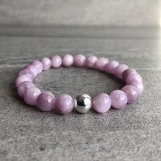 This minimalist stretch bracelet features natural Kunzite crystals. These Kunzite gemstones are naturally beautiful. The genuine Kunzite beads have gorgeous pearlescent pink hues with a hint of lilac. The simplicity of the design alllows the beauty of the stones to shine. At checkout, choose a silver or gold accent bea