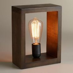 Crafted of wood with a rustic finish and an open design, our shadow box lamp features a vintage-inspired Edison bulb that fills any small space with a warm, ambient glow. This cloche-like lamp is perfect for the home office or as a unique bookend on a shelf.