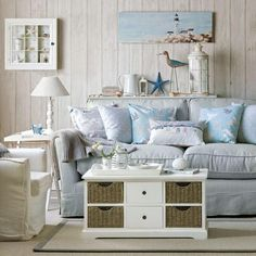 Seaside living room with white-washed wall panelling, a light blue sofa piled with cushions and an armchair, a coffee table chest and side table with lamp. Beach Cottage Style, Beach Cottage Decor, Coastal Cottage, Coastal Homes, Coastal Style, Coastal Decor, Seaside Decor, Nautical Style, Seaside Style