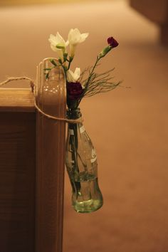 Old glass soda bottles wrapped in twine/jute and hung on church pews with fresh flowers.