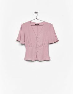 Blusa fluida botões. Descubra esta e muitas outras roupas na Bershka com novos artigos cada semana