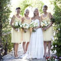 LOVE The three bridesmaids wore airy butter yellow dresses with chiffon rosettes around the scoop neckline. Chandra told them they could choose their own styles, but they all loved the same one.