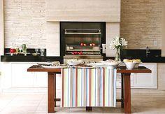 O uso do mármore Travertino Navona é a marca desta casa. A matéria-prima aparece em placas lisas, na coluna que envolve a churrasqueira, e com canjiquinha nas laterais