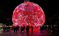 LIBSON, PORTUGAL | People stand next to a giant illuminated Christmas bauble on Rossio square