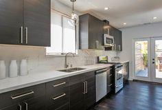 Kitchen cabinets: IKEA ; light fixture: globe pendant from West Elm, quartz countertops- *Dark Black-Brown Cabinets with silver-nickel hardware handles  *White Quartz Countertops *Stainless Steel Appliances
