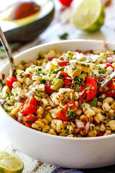 Fresh Corn Salad with avocado, red bell peppers, jalapeno, cilantro, sesame seeds mixed together in a white bowl with silver spoons