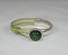 SOLD... Half brushed silver plate, half metallic green leather creating a button closure