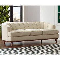 Herald the renaissance of elegant Mid-Century style with this fabulous neutral nubby cream fabric upholstered sofa.