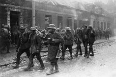 Wounded British and German troops in the streets of St Quentin, France, after the Second Battle of the Somme.
