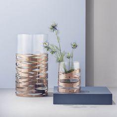 Le vase TANGLE MAGNUM de Stelton est un vase en verre en contraste avec l'éclat élégant du cuivre. La manchette en cuivre semble dynamique et donne un peu l'aspect de nostalgie au vase.