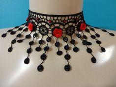 Gargantilha de renda preta, com aplicação de strass e rosas de cetim vermelhas. Possui acabamento em metal niquelado com extensor de 6cm.