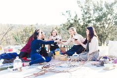Friends enjoying a picnic with champagne, wine, and blankets
