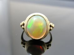 The fire in this 2.85 carat cabochon opal must be seen to be believed. Greens, oranges an yellows all sparkle an swirl inside the stone. The sturdy, simple yellow gold mounting provides and excellent frame and good protection for this unusual stone!