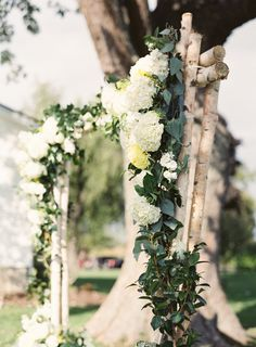 We absolutely swoon over this ceremony arbor. The birch tree arch was made for an outdoor wedding. And we love the cascading floral arrangement. This ceremony piece includes white wedding flowers and tons of greenery. It's totally charming for an outdoor rustic wedding. Photography by Kina Wicks.