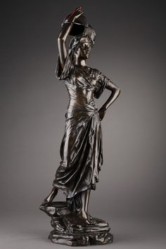 A bronze sculpture with dark brown patination representing a draped woman holding on her head an empty jar decorated with arabsques, walking towards the fountain. The pure forms of her...
