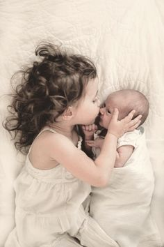 Pure love / a sister's kiss / so sweet and such a great photograph they will treasure always