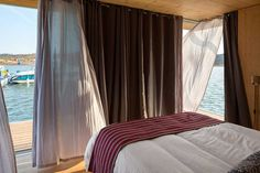 This modern bedroom on a houseboat has taken full advantage of the small space and created a full wall of sliding doors. I would love to a fresh lake breeze and hillside view!