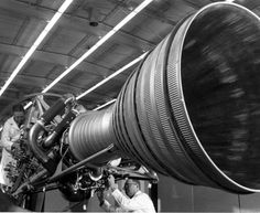 """Mechanics at work at Rocketdyne in Canoga Park, circa 1960. A related press release explains that the mechanics are making """"the final adjustments on an engine which will be used in the U.S. Army Jupiter intermediate range ballistic missile. The Jupiter IRBM will be deployed in operational use by units of the Strategic Air Command."""" San Fernando Valley Historical Society. San Fernando Valley History Digital Library."""