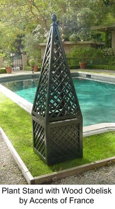 Outdoor decoration with wood plant stand with obelisk on top by Accents of France