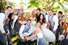 Group portrait of the wedding party in the countryside wearing blue gray and white with bride and bridesmaids carrying light pink and yellow bouquets and parasols - photo by Michael Norwood Photography