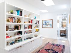 The built-in bookcase in this Malibu beach house showcases a collection of colorful books, decorative accessories and even a teddy bear. | Photographer: Amy Bartlam | Designer: Veneer Designs